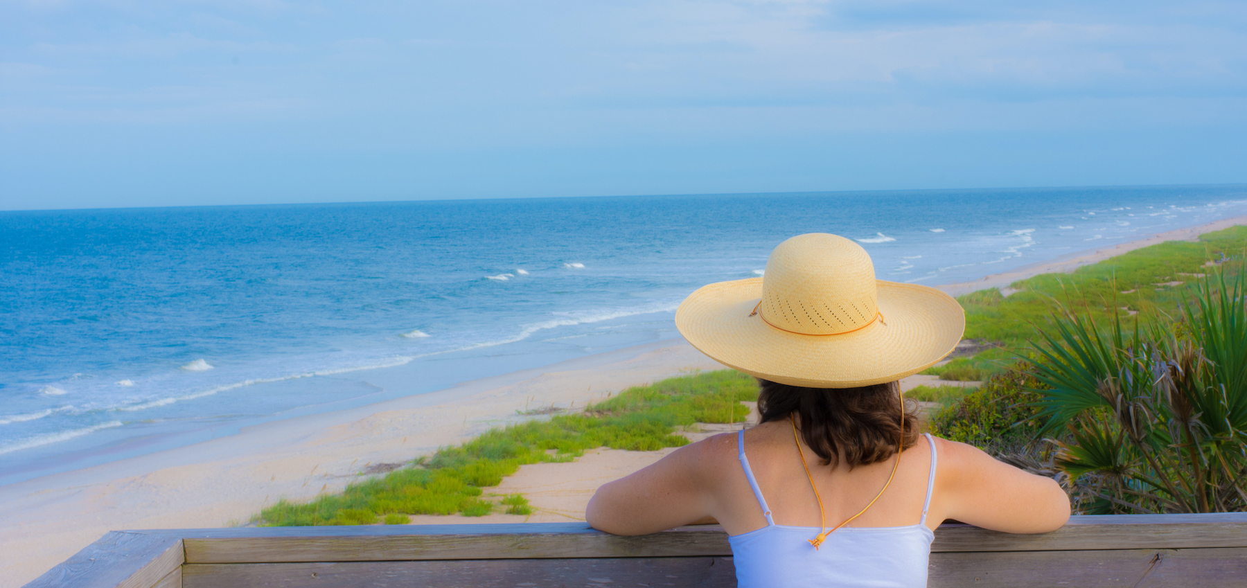 woman with brown hair white tank top and sunhat on pier looking out at st augustine beach in saint augustine florida