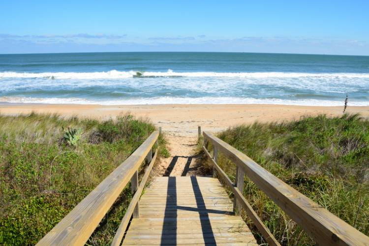 boardwalk to st augustine beach in florida with waves crashing on the shore and bright blue skies