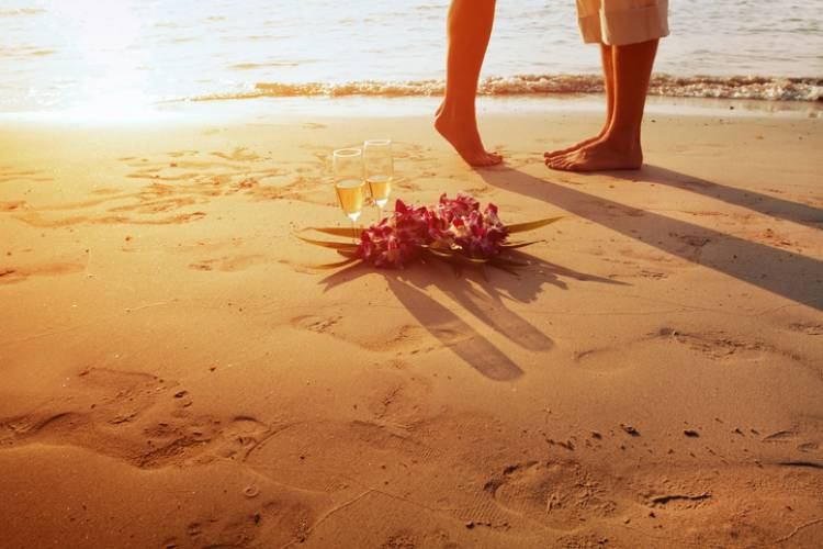 view of two people's feet, one on tip toes, and flowers in the foreground as the sunsets in the background on the beach
