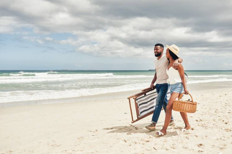 young couple walking along the beach with chairs and picnic items in hand
