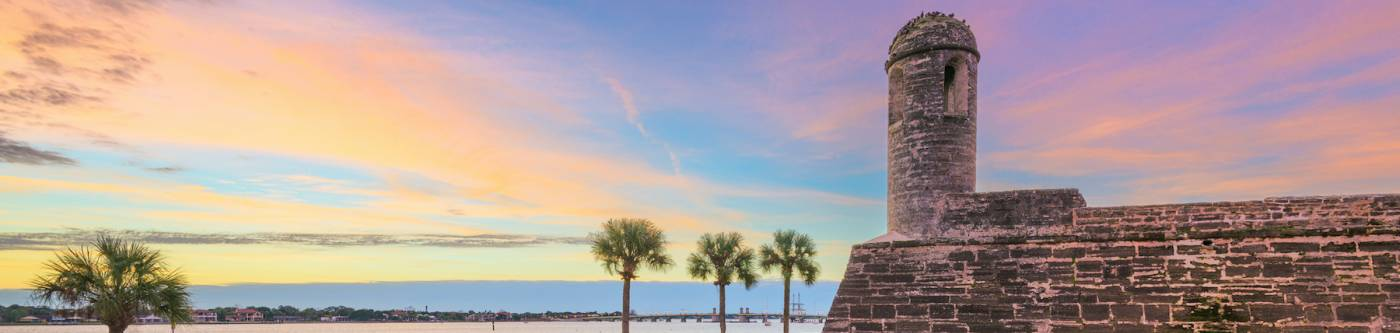 purple, blue, yellow sky over castillo de san marcos in st augustine florida with four palm trees along the water
